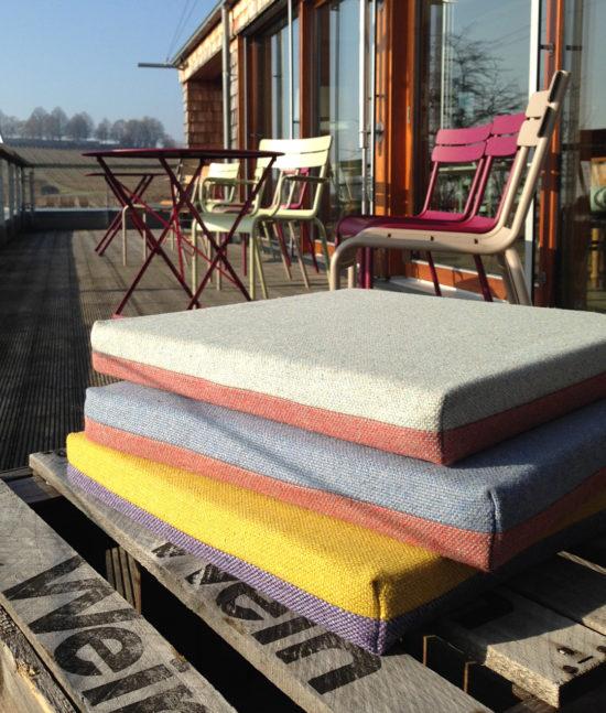 Sitz Kissen aus Schurwolle auf Weinkisten gestapelt auf Terrasse. Chair cushions from new wool on wine box on terrace