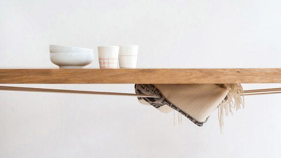 Ausschnitt der 40mm starken Eichen Tischplatte mit weißem Porzellen und Wolldecke, die in den Gummiseilen unter die Tischplatte geklemmt ist.