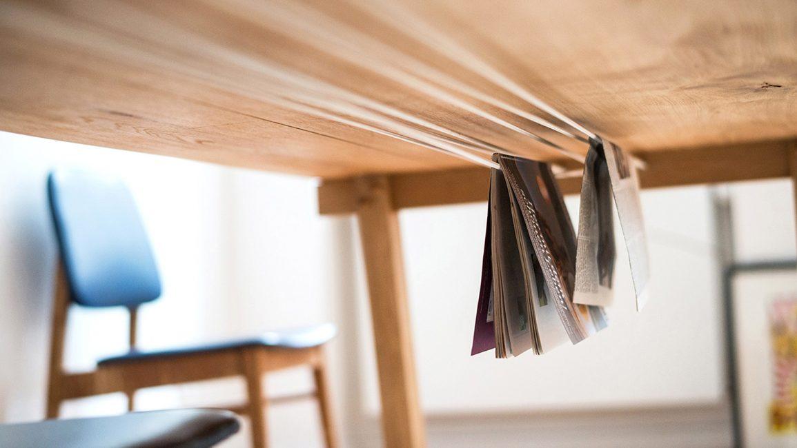 Unter der Tischplatte in Gummiseilen abgehangene Zeitschriften.